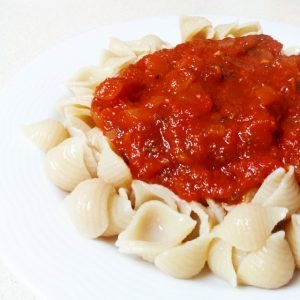 אטריות אורז חום מלא עם רוטב עגבניות עשיר בניחוח בזיליקום, שום ובצל.